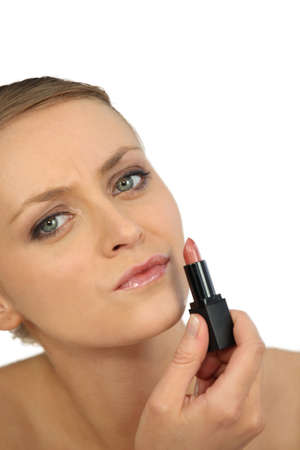 woman putting lipstick Stock Photo - 16670498