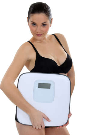 Woman in underwear carrying scales Stock Photo - 16670661