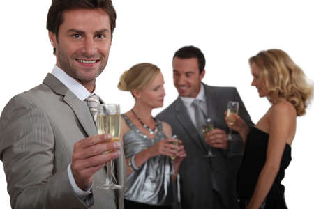 30 34 years: Man making a toast with champagne as his friends chat in the background