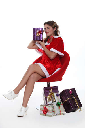 Woman dressed as Mrs  Claus holding a present Stock Photo - 16670834