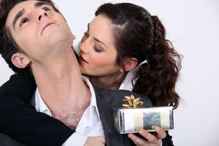 Woman kissing her partner for a present Stock Photo - 16669437