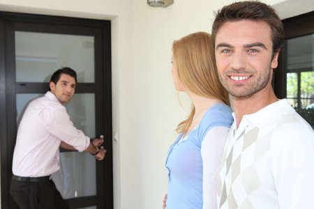 Estate-agent opening door to show home photo