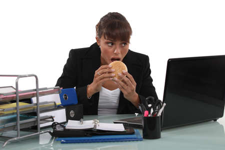 Woman eating a burger at her desk Stock Photo - 16670699