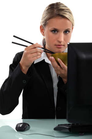 Woman sitting at her computer eating with chopsticks Stock Photo - 16670501