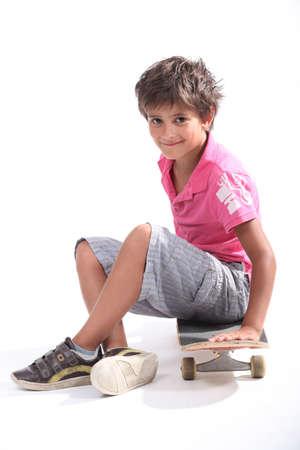 skaters: Child sitting on his skateboard