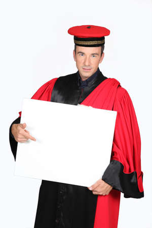 Man in red and black robe and cap pointing at board blank for text Stock Photo - 16670609