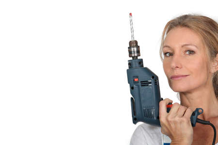 electric drill: Blond woman holding electric drill