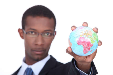 Concept shot of a businessman holding a miniature globe photo