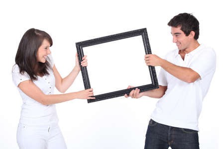 Couple fighting over blank picture frame photo