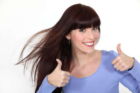 Brunette giving thumbs-up gesture Stock Photo - 16669642