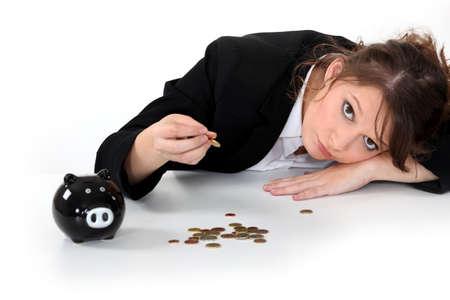 desperate: Chica contando el dinero de su hucha Foto de archivo