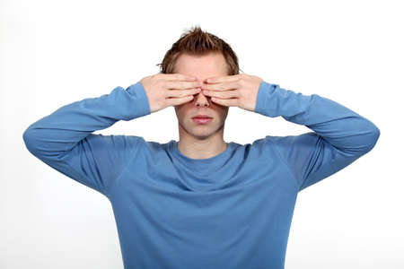 Young man covering his eyes photo