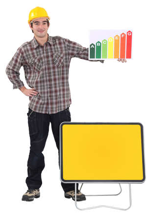 tradesman: Tradesman standing before a blank sign and holding an energy efficiency rating chart Stock Photo