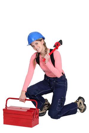 woman kneeling: Woman kneeling by tool box Stock Photo