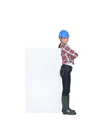Female construction worker with a board left blank for your message photo