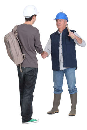 warm welcome: Manual worker giving new starter a warm welcome Stock Photo