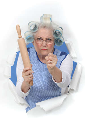 angry woman: Angry old woman with a rolling pin Stock Photo