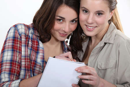 Two girls writing on a notebook photo