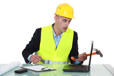 clumsy: Clumsy architect smashing laptop with hammer Stock Photo