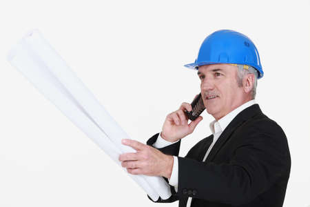 construction management: Grey-haired architect with plans Stock Photo