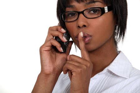 Black businesswoman making hush gesture during phone call Stock Photo - 16670267