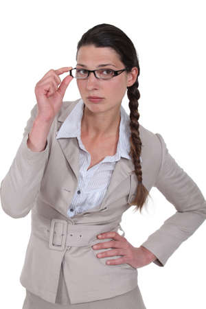 exacting: Stern businesswoman touching glasses Stock Photo