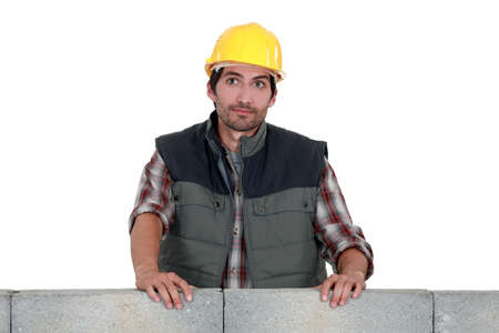 erecting: craftsman leaning on a stone block wall Stock Photo