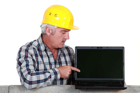 Tradesman pointing to his new laptop Stock Photo - 16670164