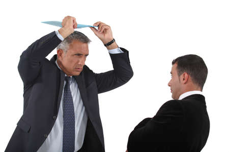 angry boss: Angry boss about to hit employee with clip-board Stock Photo