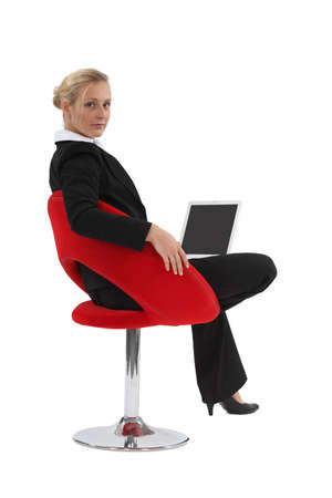 Woman sitting in a chair and using her laptop photo