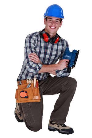Man with power sander kneeling Stock Photo - 16670216