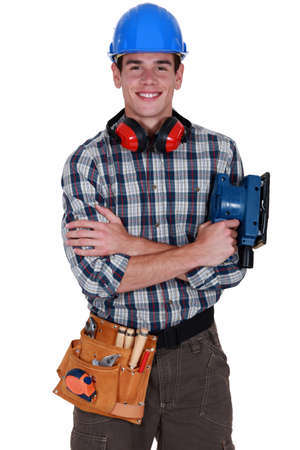 fulfilled: Young tradesman holding a sander Stock Photo