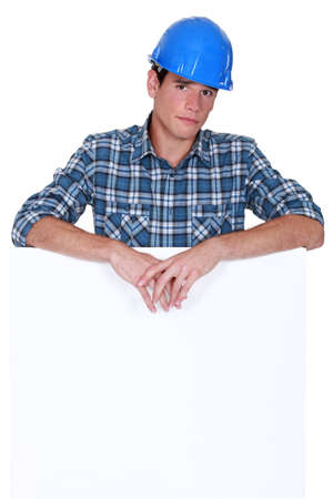 Downbeat manual worker stood with blank poster photo