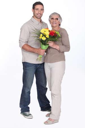 madre e hijo: Son regalar flores madre Foto de archivo