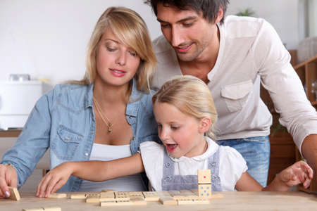 play room: happy couple playing rectangular blocks  with daughter Stock Photo