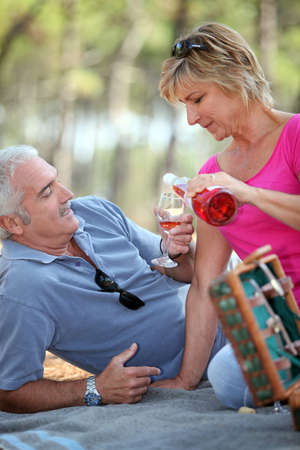 Middle-aged couple having fancy picnic photo
