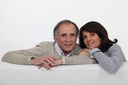 Mature couple leaning on back of sofa photo