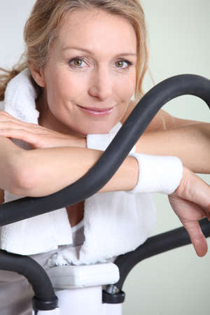 Woman using cycling machine to stay fit Stock Photo - 16669869