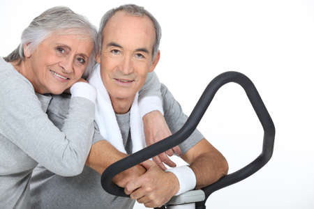 Sporty senior couple with cross trainer