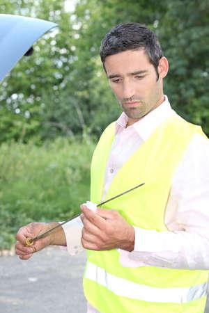 Man checking his oil dipstick Stock Photo - 16669510