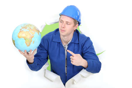 young apprentice in jumpsuit pointing at globe Stock Photo - 16730483
