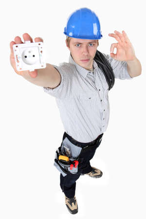 electrician holding an electrical socket and making an okay sign photo