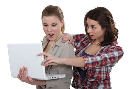 bombshell: Two shocked girls looking at laptop Stock Photo