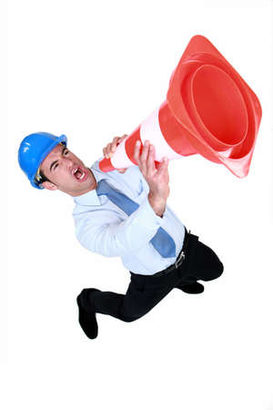 Man using a traffic cone as a loudspeaker Stock Photo