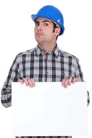 cagey: Unsure construction worker holding up a blank sign Stock Photo