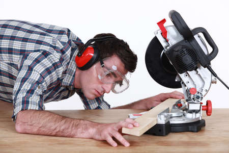 tradesperson: Man positioning a plank of wood in a mitre saw Stock Photo