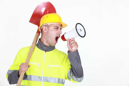 Worker with a spade screaming into a bullhorn photo