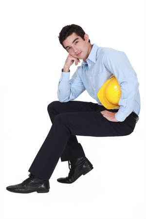 niewidoczny: Młody inżynier siedzi na niewidocznym stolcu