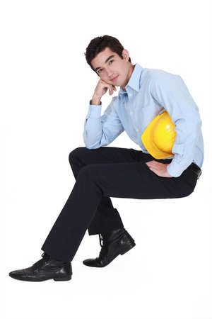 Young engineer sitting on an invisible stool photo