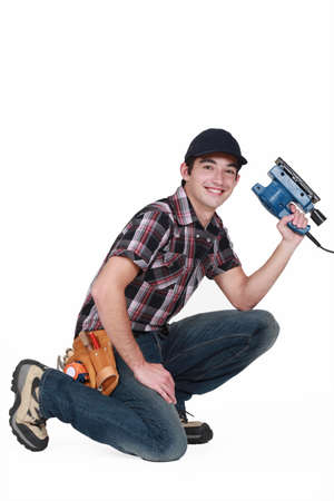 smoothen: Young man holding a sander